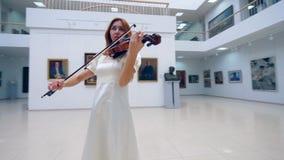 Um músico joga o violino ao executar em um museu apenas vídeos de arquivo