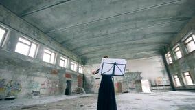 Um músico joga o violino em uma construção com grafittis em paredes filme