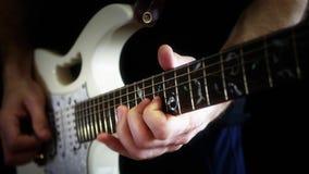 Um músico joga só em uma guitarra elétrica branca em um fundo preto O homem está jogando a rocha video estoque