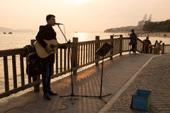 Um músico novo da rua que canta ao longo da praia na cidade de Xiamen, China Imagem de Stock