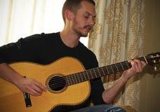 Um músico Plays uma guitarra acústica clássica fotografia de stock royalty free