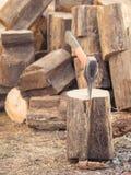 Um machado com um punho alaranjado e uma grande pilha do bloco de madeira de madeira Imagens de Stock Royalty Free