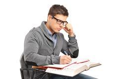 Um macho novo nos pensamentos que fazem um exame Foto de Stock