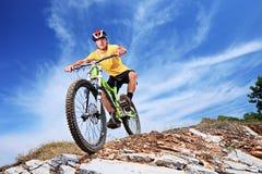 Um macho novo que monta uma bicicleta de montanha Fotos de Stock Royalty Free