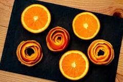 Um mandarino é servido em uma pedra escura com uma decoração de um citrino da casca foto de stock