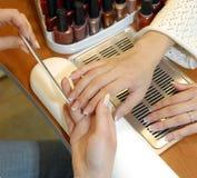 Um manicure está em um salão de beleza de beleza Fotografia de Stock Royalty Free
