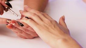 Um manicuro com pregos pretos cobriu a unha do ` s da menina no dedo pequeno de sua mão com um verniz brilhante Close-up filme