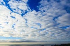 Um mar das nuvens cobre o céu azul fotografia de stock