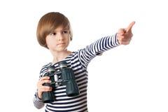 Um marinheiro pequeno com pontos binoculares por um dedo Fotografia de Stock Royalty Free