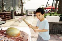 Um martelo da criança um ovo dourado Imagem de Stock