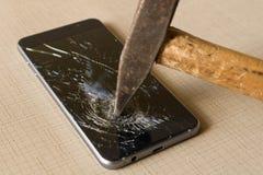 Um martelo que despedaça um telefone celular em um fundo cinzento imagens de stock
