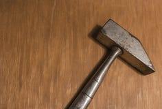 Um martelo velho em uma superfície de madeira fotografia de stock royalty free