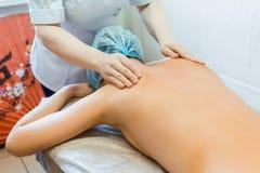 Um massagista fêmea faz uma massagem traseira a uma moça em um salão de beleza dos termas A menina encontra-se na tabela da massa fotos de stock royalty free