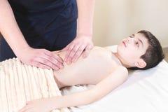 Um massagista masculino do fisioterapeuta faz uma massagem de relaxamento da cura a um menino de sorriso pequeno que encontra-se  foto de stock royalty free