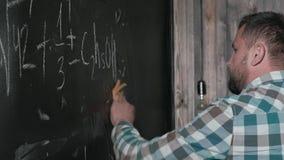 Um matemático maduro brilhante traz uma placa grande e termina uma equação complicada ensaio da fórmula matemática vídeos de arquivo