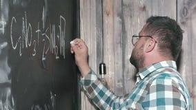 Um matemático maduro brilhante traz uma placa grande e termina uma equação complicada ensaio da fórmula matemática filme