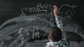 Um matemático maduro brilhante traz uma placa grande e termina uma equação complicada ensaio da fórmula matemática video estoque