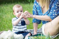 Um mather bonito que dá a água de uma garrafa com uma chupeta a um assento do bebê exterior na grama Fotos de Stock Royalty Free