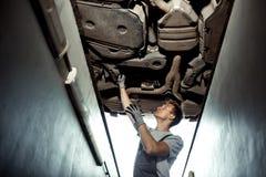 Um mecânico de carro está verificando um carro levantado Manutenção do carro fotos de stock