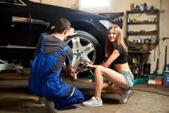Um mecânico masculino em um terno do azul repara um pneu de carro Foto de Stock