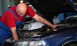Um mecânico que repara um carro imagens de stock