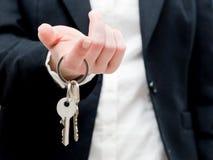 Um mediador imobiliário que guarda chaves a uma casa nova em suas mãos. Foto de Stock Royalty Free