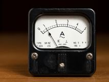 Um medidor análogo preto velho do ampère em uma tabela de madeira imagem de stock