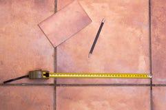 Um medidor com uma pena para medir a telha no assoalho Imagem de Stock