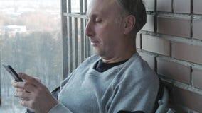Um meio envelheceu olhares do homem em fotos em um smartphone e em sorrisos Memórias agradáveis filme