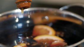 Um mel está gotejando em uma bandeja com vinho ferventado com especiarias vídeos de arquivo