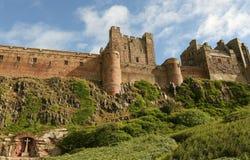 Um memorial de guerra ajustou-se em uma alcova na rocha abaixo do castelo de Bamburgh em Northumberland Inglaterra imagens de stock royalty free