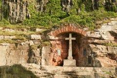 Um memorial de guerra ajustou-se em uma alcova na rocha abaixo do castelo de Bamburgh em Northumberland Inglaterra fotos de stock royalty free