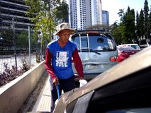 Um mendigo cego que pede a esmola entre motoristas em uma estrada principal na cidade de Pasig, Filipinas imagem de stock