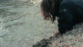 Um mendigo desabrigado encontra-se perto do rio e lava-se suas mãos e cara vídeos de arquivo