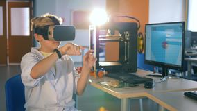 Um menino adolescente em vidros da realidade virtual está tirando algo no ar com suas mãos filme