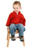 Um menino adorável dos anos de idade que senta-se no tamborete de etapa Foto de Stock