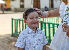 Um menino agradável sorri muito feliz quando sua mãe correr sua mão através do cabelo molhado foto de stock