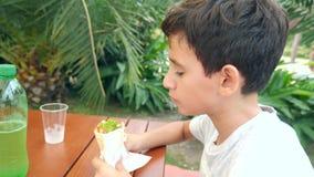 Um menino atrativo come um pão árabe do pão fresco com uma salada de legumes frescos e de carne, sentando-se em um café do fast f vídeos de arquivo