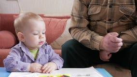 Um menino atrativo de 2 anos e o avô tiram animais com um marcador Decoração home filme