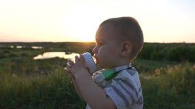 Um menino bonito bebe uma compota de uma garrafa de bebê fora no movimento lento vídeos de arquivo