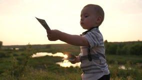 Um menino bonito dá cem notas de dólar para uma conta a um adulto no movimento lento vídeos de arquivo