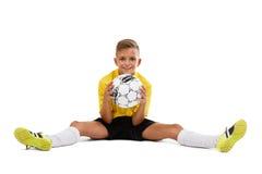 Um menino bonito em um amarelo ostenta posses do uniforme uma bola em suas mãos, jogador de futebol novo isolado em um fundo bran Foto de Stock