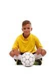 Um menino bonito em um uniforme amarelo do esporte guarda uma bola em suas mãos isoladas em um fundo branco Fotos de Stock Royalty Free