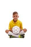 Um menino bonito em um uniforme amarelo do esporte guarda uma bola em suas mãos isoladas em um fundo branco Imagens de Stock Royalty Free