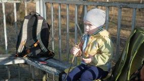 Um menino bonito está comendo uma salsicha fora Cozinhado no BBQ do fogo filme