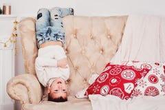 Um menino bonito está estando em sua cabeça no sofá Um indivíduo desportivo em um branco fez malha a camiseta e as calças de brim Fotos de Stock