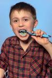 Um menino bonito no dentes das escovas dos pijamas com dentífrico antes das horas de dormir em um fundo azul imagem de stock royalty free