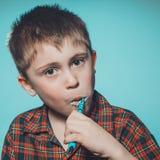 Um menino bonito no dentes das escovas dos pijamas com dentífrico antes das horas de dormir em um fundo azul fotos de stock royalty free
