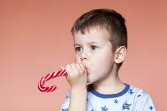 Um menino bonito que come varas dos doces Bastões de doces feitos a mão tradicionais coloridos fotografia de stock royalty free