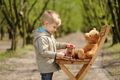 Um menino bonito que senta-se na cadeira com o urso de peluche na primavera Árvore côr de avelã imagens de stock